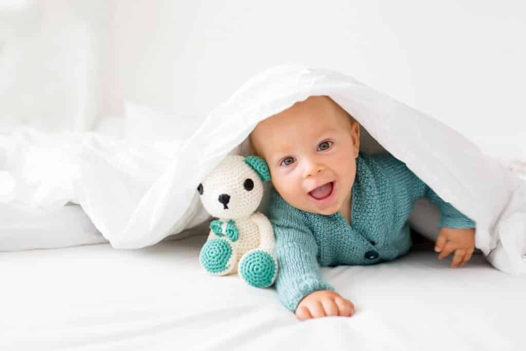 bébé sous une couette blanche
